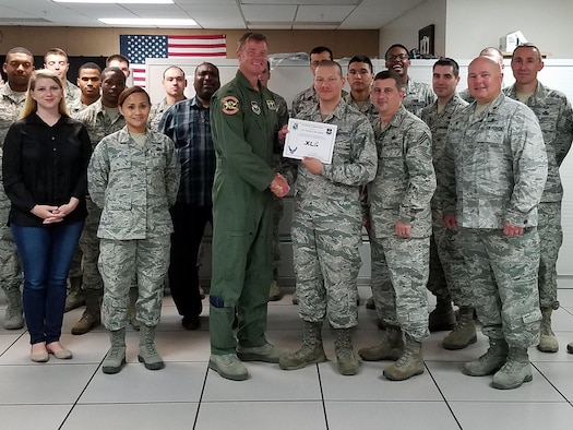 "Airman 1st Class Patrick Bova-Ruiz, 47th Communications Squadron fiber transport technician, accepts the ""XLer of the Week"" award from Col. Thomas Shank, left, 47th Flying Training Wing commander, and Chief Master Sgt. George Richey, 47th FTW command chief, here, July 6, 2016. The XLer is a weekly award chosen by wing leadership and is presented to those who consistently make outstanding contributions to their unit and Laughlin. (Courtesy photo)"