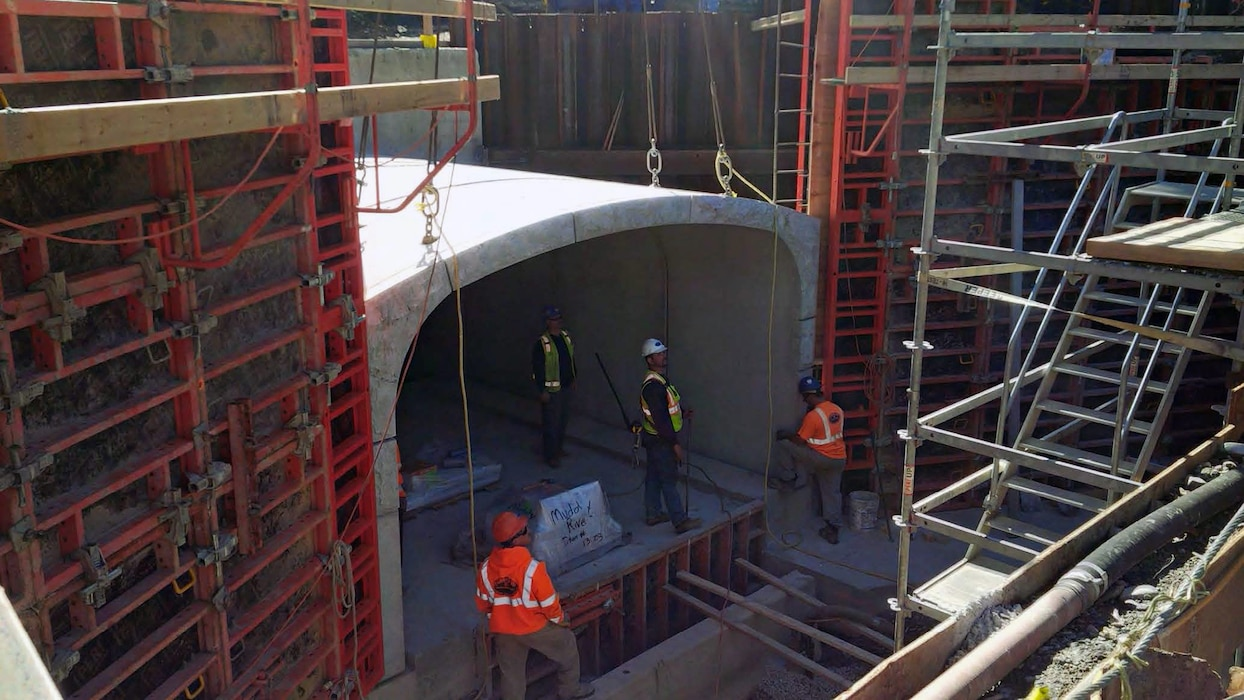 Installation of a precast concrete culvert section. Note the attached granite veneer on the culvert face and the formwork and rebar for the wingwalls on either side of the precast culvert – mid October 2015.