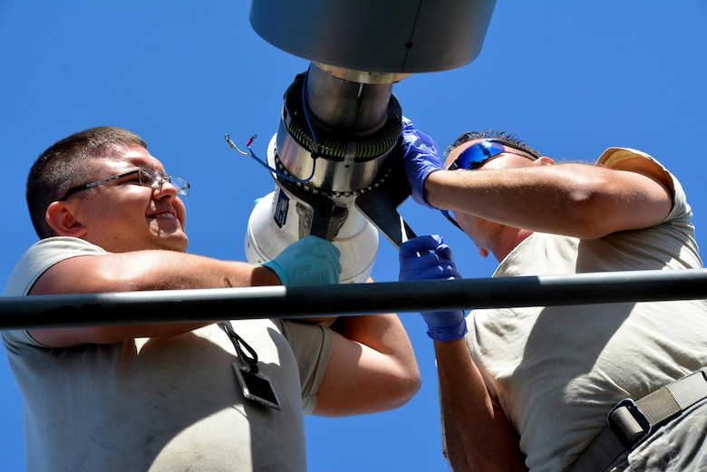 JOINT BASE PEARL HARBOR-HICKAM (July 10, 2016) (from left to right) Staff Sgt. James Andrus  and Senior Airman Travis Krause, U.S. Air Force crew chiefs with the 507th Aircraft Maintenance Squadron at Tinker Air Force Base, Okla., use expander wrenches to remove the boom nozzle from a KC-135R Stratotanker in order to connect a drogue adapter and drogue. The probe and drogue method of refueling uses a trailing hose with a basket on the end. Pilots guide a probe on their aircraft into the basket to connect with the hose. Air Force helicopters and all Navy and Marine Corps aircraft refuel using the hose-and-drogue for air-to-air refueling. Andrus, Krause and other Citizen Airmen are participating in the 25th Rim of the Pacific Exercise, which began in 1971 Twenty-six nations, more than 40 ships and submarines, more than 200 aircraft, and 25,000 personnel are participating in RIMPAC from June 30 to Aug. 4, in and around the Hawaiian Islands and Southern California. RIMPAC is the world's largest international maritime exercise, which provides a unique training opportunity that helps participants foster and sustain cooperative relationships that are critical to ensuring the safety of sea lanes and security on the world's oceans. (U.S. Air Force photo/Master Sgt. Grady Epperly/Released)