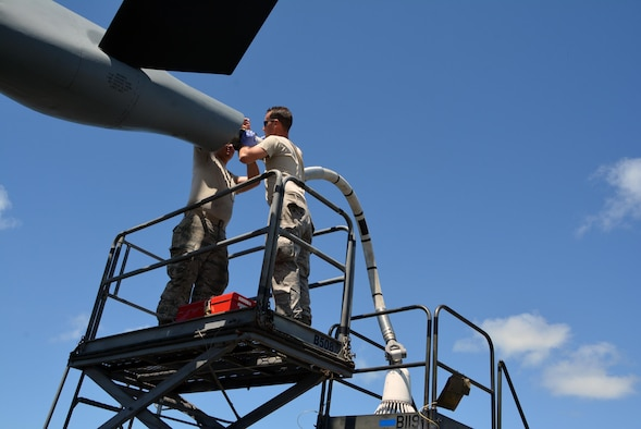 Staff Sgt. James Andrus and Senior Airman Travis Krause, U.S. Air Force crew chiefs with the 507th Aircraft Maintenance Squadron at Tinker Air Force Base, Okla., connect a drogue adapter to a KC-135R Stratotanker in order to connect a drogue. A drogue is used in air-to-air refueling. The probe and drogue method of refueling uses a trailing hose with a basket on the end. Pilots guide a probe on their aircraft into the basket to connect with the hose. Air Force helicopters, and all Navy and Marine Corps aircraft refuel using the hose-and-drogue for air-to-air refueling. Andrus, Krause and other Citizen Airmen are participating in Rim of the Pacific exercise 2016. (U.S. Air Force photo/Master Sgt. Grady Epperly/Released)