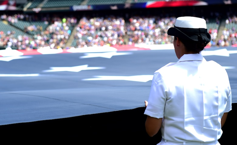 A Service member holds an American flag July 10, 2016, during a military appreciation ceremony at a Colorado Rockies game at Coors Field in Denver. The ceremony included the flag stretched out in the outfield, the singing of the National Anthem and the ringing of the Honor Bell. (U.S. Air Force photo by Airman 1st Class Gabrielle Spradling/Released)