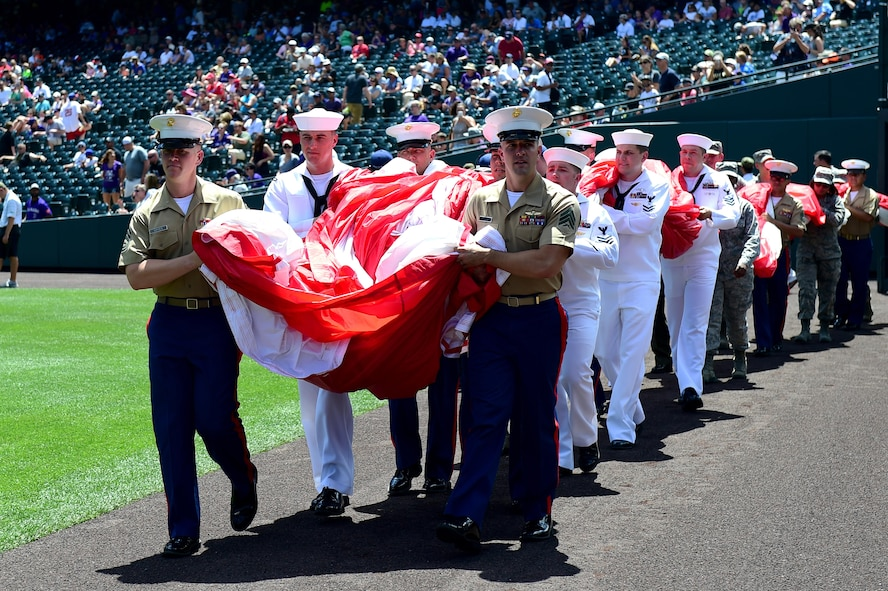 Service members carry out an American flag July 10, 2016, during a military appreciation ceremony at a Colorado Rockies game at Coors Field in Denver. The ceremony brought together members from every branch of the military to honor those who have served or are currently serving in the military. (U.S. Air Force photo by Airman 1st Class Gabrielle Spradling/Released)