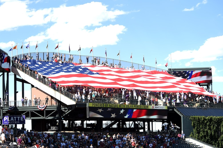 Service members unravel an American flag July 10, 2016, during the seventh inning stretch at a Colorado Rockies military appreciation game at Coors Field in Denver, Colo. The ceremony provided an opportunity to recognize Service members from every branch and their sacrifices. (U.S. Air Force photo by Airman 1st Class Gabrielle Spradling/Released)