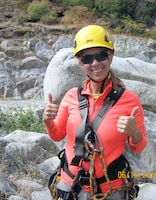 Coralie Wilhite, a geological engineer for the U.S. Army Corps of Engineers Sacramento District, gives the thumbs up after rappelling down a rock face along the bank of the American River near Folsom Dam to mark rock bolt anchor locations as part of the Joint Federal Project.