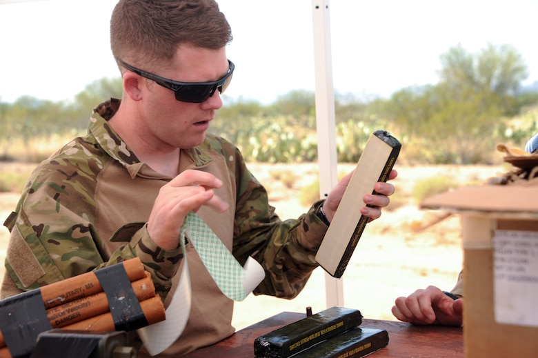 U.S. Air Force Staff Sgt. Michael McNally, 355th Maintenance Group scheduler, removes the cover from an adhesive strip on a block of C4 plastic explosive during an explosive ordnance disposal immersion course at Davis-Monthan Air Force Base, Ariz., June 28, 2016. McNally has worked in the maintenance support field for the past eight years. (U.S. Air Force photo by Airman Nathan H. Barbour/Released)