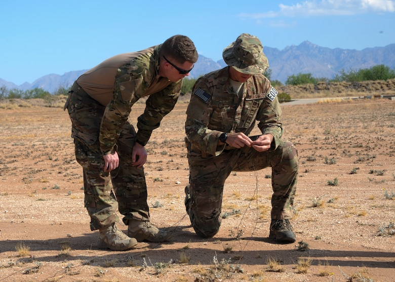 U.S. Air Force Tech. Sgt. David Collins, 355th Civil Engineer Squadron explosive ordnance disposal flight NCO in charge of training, explains the differences between two  ways to set up electric circuits for demolition to Staff Sgt. Michael McNally, 355th Maintenance Group scheduler, during an EOD immersion course at Davis-Monthan Air Force Base, Ariz., June 28, 2016. The immersion course serves a dual purpose of showing Airmen interested in retraining into EOD exactly what the specialty's technicians do on a regular basis and also determines if the candidate is right for the job. (U.S. Air Force photo by Airman Nathan H. Barbour/Released)