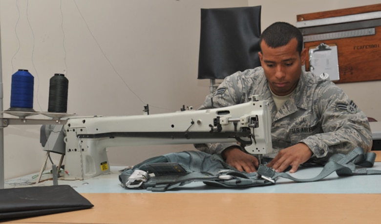 Senior Airman Kyle Boddie, 92nd Operations Support Squadron aircrew flight equipment journeyman, sews a pocket to a restraining harness July 7, 2016, at Fairchild Air Force Base, Wash. The restraining harness is used to attach an aircrew member to the jet in case of an emergency. As an aircrew flight equipment journeyman, Boddie fixes restraining harnesses, packs and inspects escape slides, 20-man life rafts, infant cots, adult and child life jackets, HGU 55/P pilot helmets and MBU 20/P 12/P oxygen breathing masks. (U.S. Air Force photo/Staff Sgt. Samantha Krolikowski)