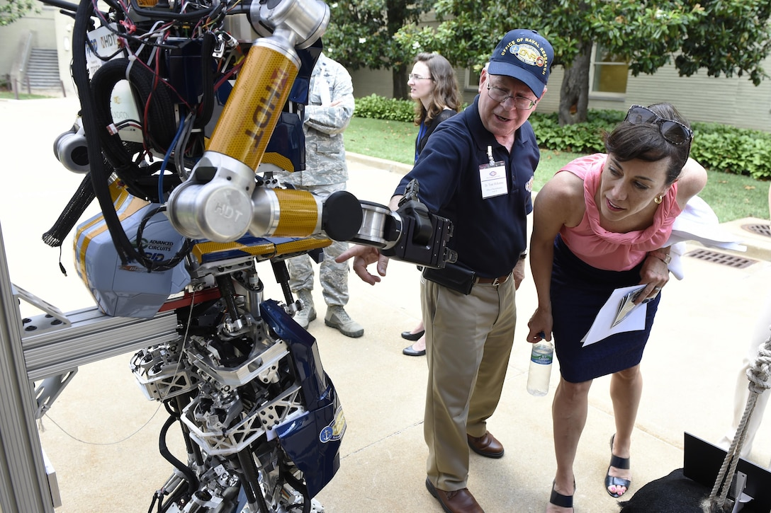 Dr. Tom McKenna, a program officer with the Office of Naval Research, talks to Dr. Janine Davidson, undersecretary of the Navy, about the Shipboard Autonomous Firefighting Robot during a Technology Innovation Day event at the Pentagon, June 24, 2016. Navy photo by John F. Williams