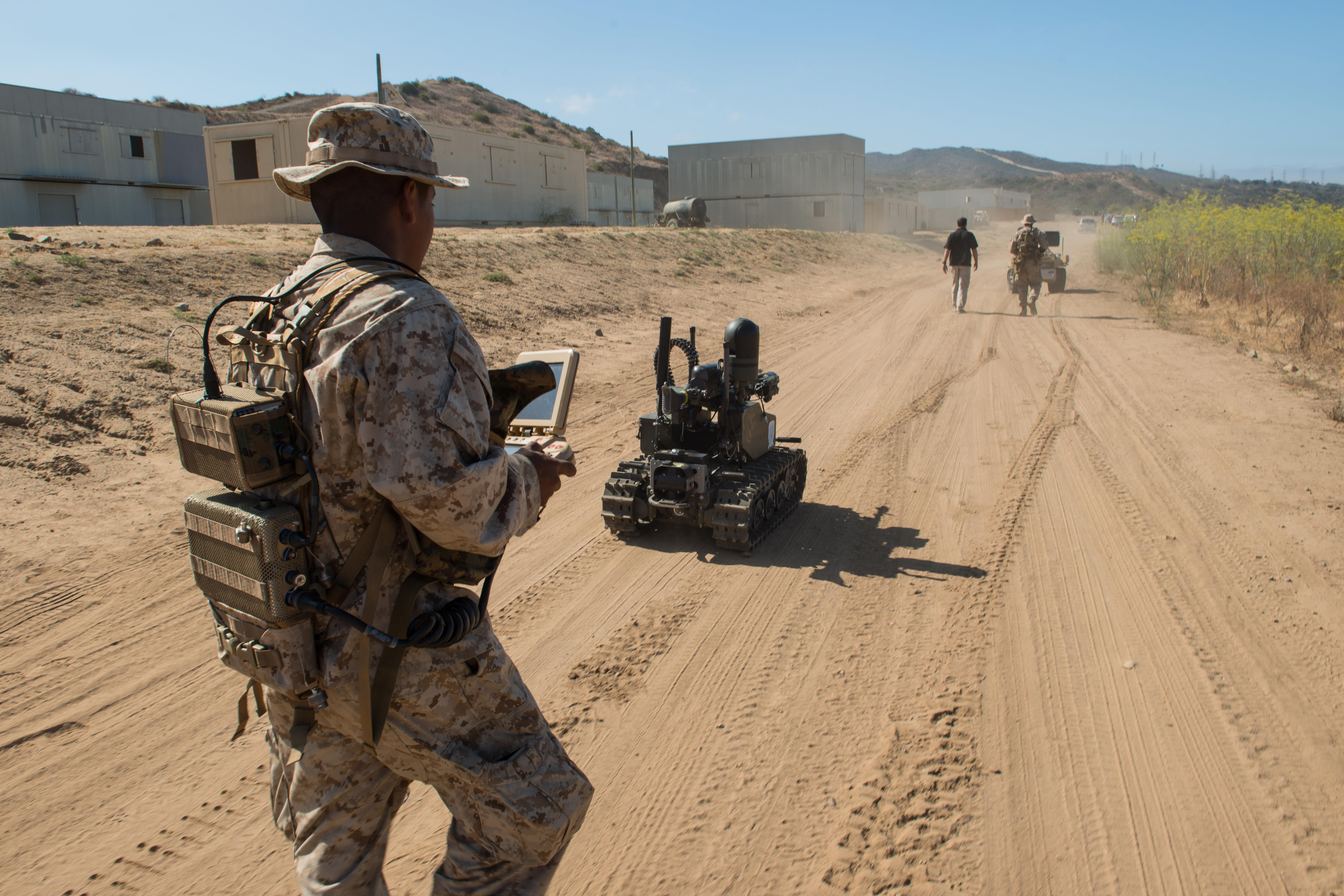 Marine Corps Pfc. Edgar Langle operates a newly developed Modular Advanced Armed Robotic System in a field environment