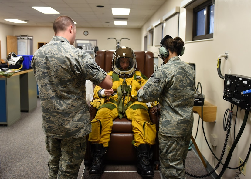 Tech. Sgt. Shawn Rose (left), and Senior Airman Christian Mitchell, 9th Physiological Support Squadron aerospace physiology technicians, assist Lt. Col. Nicole Mann, United States Marine Corps, NASA astronaut, with a full-pressure suit July 7, 2016, at Beale Air Force Base, California. Mann is undergoing Space Flight Readiness Training. (U.S. Air Force photo/ Senior Airman Bobby Cummings)