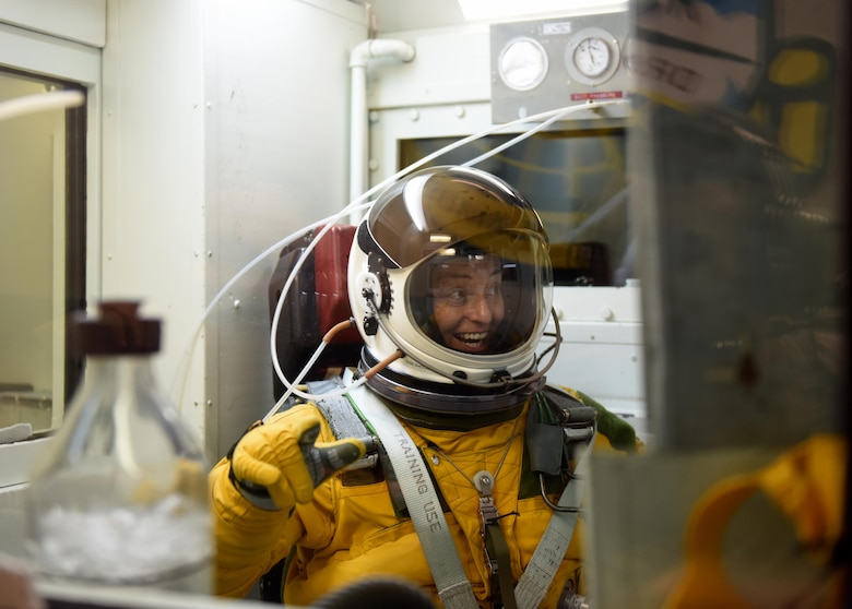 Lt. Col. Nicole Mann, United States Marine Corps, NASA astronaut, reacts to boiling water inside a hypobaric chamber July 7, 2016, at Beale Air Force Base, California. Mann reached simulated altitudes exceeding Armstrong's line (63,000 ft.) in the chamber. Atmospheric pressure at Armstrong's line is so low water boils at the normal temperature of the human body. (U.S. Air Force photo/ Senior Airman Bobby Cummings)