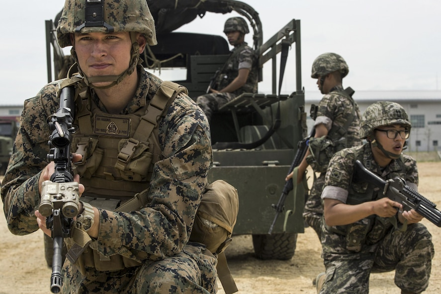 Marine Corps Cpl. Beau M. Higgins posts security beside a South Korean marine.