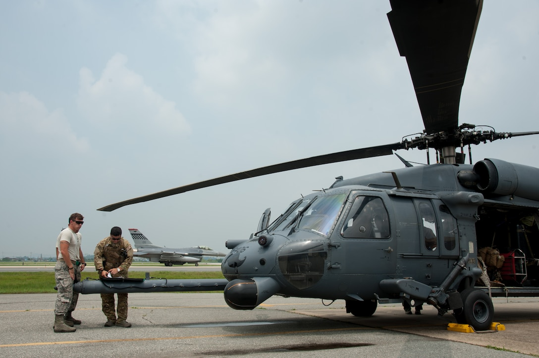 SSgt Brandon McCown, 33rd Helicopter Maintenance Unit crew chief, and Master Sgt. Vincent, 33rd Rescue Squadron special mission aviator, review a preflight checklist before flight during Exercise Pacific Thunder 16-2 at Osan Air Base, Republic of Korea, July 12, 2016. The 33rd RQS is participating in Pacific Thunder, the largest Air Force combined joint combat search and rescue exercise in the Pacific. (U.S. Air Force photo by Staff Sgt. Jonathan Steffen/Released)