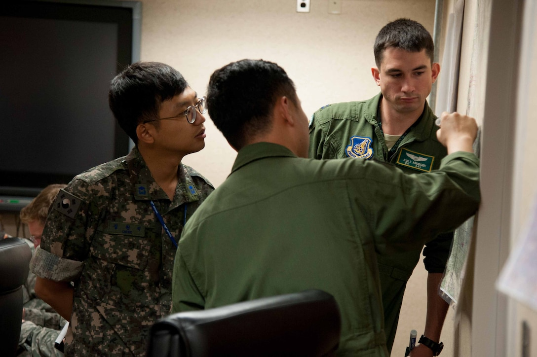 Republic of Korea air force 2nd Lt. Wonseog Chung, Air Force Operations Command combined coordinator translator, ROKAF Capt. Hatae Wook, 123rd Fighter Squadron pilot, and Capt. Zachary Krueger, 25th Fighter Squadron pilot, plan a mission for Exercise Pacific Thunder 16-2 at Osan Air Base, Republic of Korea, July 13, 2016. Pacific Thunder is the largest Pacific combined joint exercise in which U.S. and ROK forces train and test combat search and rescue skills. (U.S. Air Force photo by Staff Sgt. Jonathan Steffen/Released)