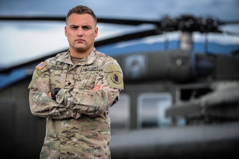 U.S. Army Spc. Tyler Holman, a combat medic assigned to the 1st Battalion, 228th Aviation Regiment, poses for a photo in front of a UH-60 Black Hawk at Soto Cano Air Base, Honduras, July 12, 2016. Holman administered CPR to an unresponsive Honduran teen and helped transport her to a hospital. (U.S. Air Force photo by Staff Sgt. Siuta B. Ika)