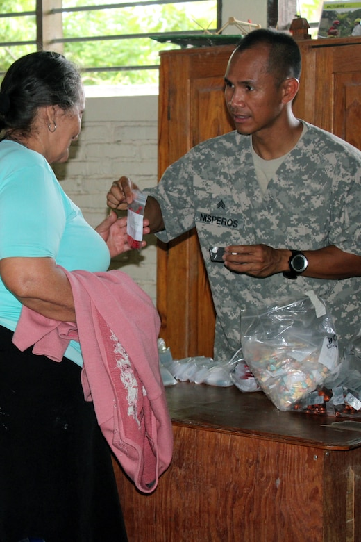 Comayagua, Honduras – U.S. Army Sergeant Jason Nisperos, Joint Task Force-Bravo preventive medicine NCO, hands multivitamins and deworming medication to a Honduran woman during a Military Partnership Engagement between JTF-Bravo and the Experimental Center of Agricultural Development and Ecological Conservation (CEDACE) in San Sebastian, Comayagua, Honduras, July 9, 2016. JTF-Bravo participated on the mission at the request of the Military Commander of CEDACE.  (U.S. Army photo by Maria Pinel)