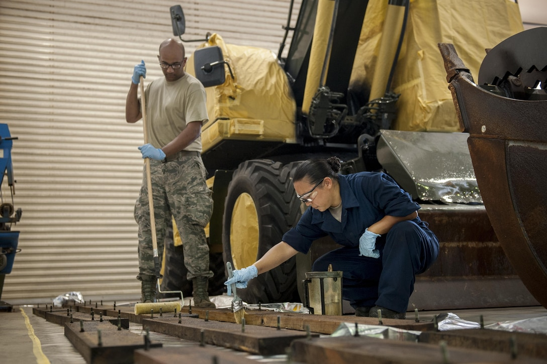 U.S. Air Force Reserve Staff Sergeants Larry Green and Amber Melgoza-Kulesza, both 944th Logistics Readiness Squadron vehicle maintenance journeymen, assigned to Luke Air Force Base, Ariz., apply linseed oil to trailer planks as part of an airfield damage repair anti-corrosion project, July 7, 2016, at Kadena Air Base, Japan. The anti-corrosion project maximizes the life ADR equipment while saving the Air Force approximately $2-3 million with a $90,000 investment in anti-corrosion materials. Upon completion of Kadena's ADR program, Air Force leaders plan to use it as a benchmark by which to set a new Air Force standard. (U.S. Air Force photo by Senior Airman Peter Reft) (This image was enhanced using multiple filters and dodging and burning techniques)