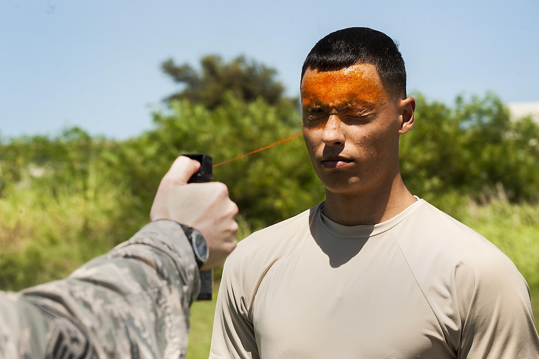 U.S. Air Force Airman 1st Class Dustin Sullivan, 18th Security Forces Squadron response force member, gets sprayed in the eyes with OC spray during training July 13, 2016 at Kadena Air Base, Japan. In order to be certified to use OC spray, SFS members must be sprayed and complete an obstacle course involves M-9 pistol reloading, subduing someone in a red-man suit and carrying water jugs around cones. (U.S. Air Force photo by Airman 1st Class Corey M. Pettis)