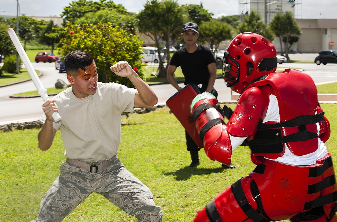 U.S. Air Force Airman Joshua Lenaire, 18th Security Forces Squadron response force member, uses a training baton to subdue an attacker in a red-man suit after being sprayed with OC spray during training July 13, 2016, at Kadena Air Base, Japan. Every SFS member must train to use OC spray by getting sprayed and completing an obstacle course. (U.S. Air Force photo by Airman 1st Class Corey M. Pettis)