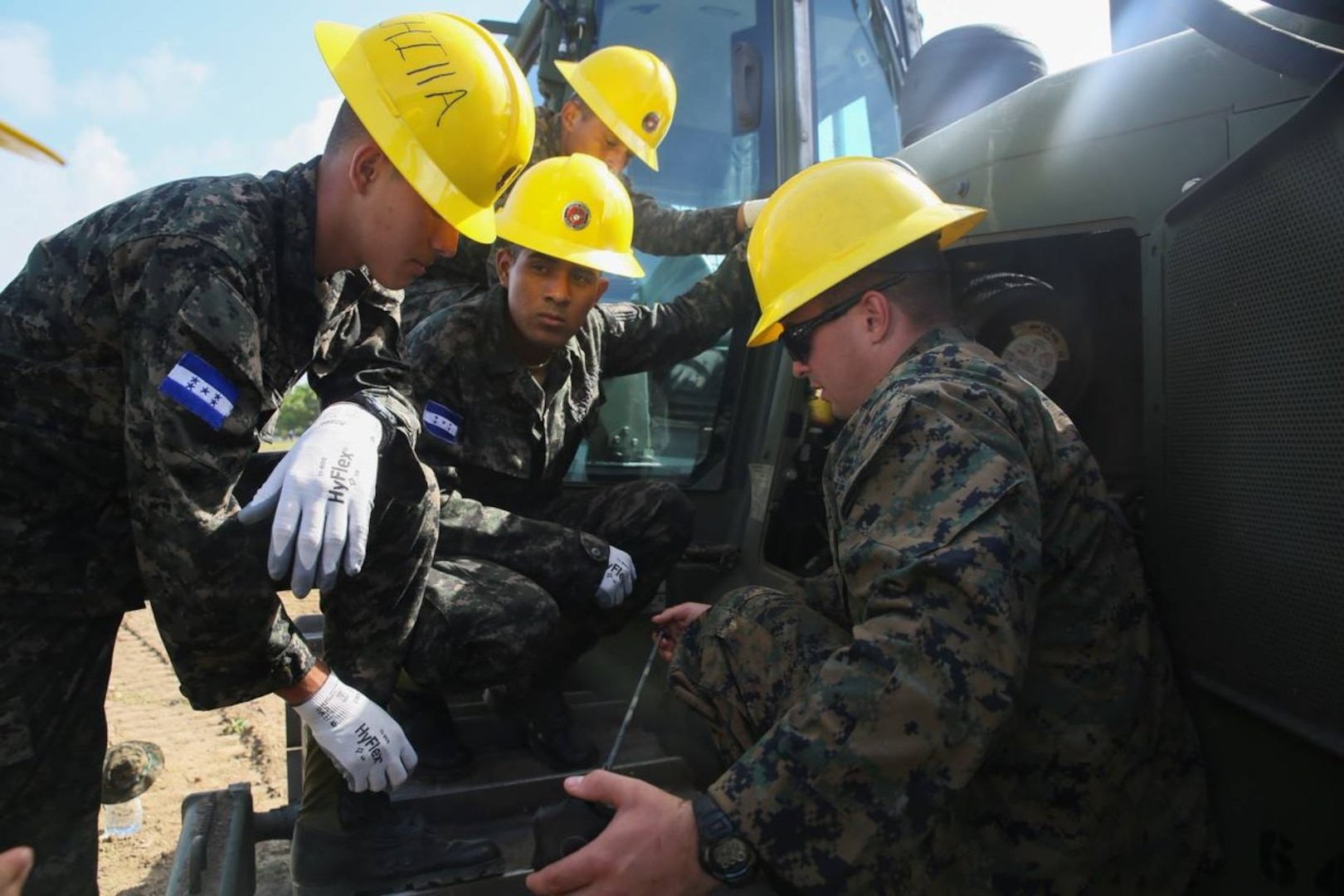 Marine Corps Cpl. Kaleb R. Hougland, senior heavy equipment mechanic with Special Purpose Marine Air-Ground Task Force-Southern Command, inspects a bulldozer during a construction project with Honduran service members and U.S. Marines at Puerto Castilla, Honduras, June 24, 2016. The Marines worked with Honduran engineers on construction and restoration projects and shared knowledge and experience. Marine Corps photo by Cpl. Ian Ferro