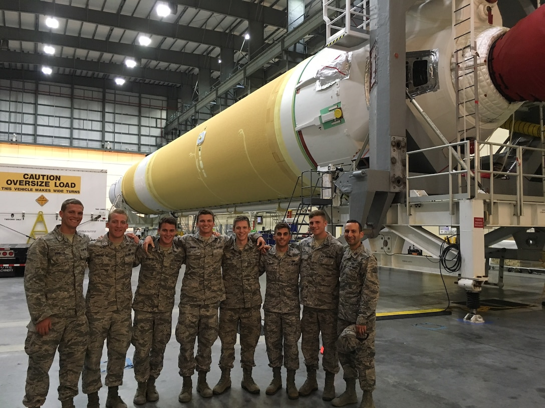 Cadets from the United States Air Force Academy pose for a photo in front of a Delta IV engine at the Horizontal Integration Facility at Cape Canaveral Air Force Station, Fla., June 15, 2016. The cadets visited the 45th Space Wing as a part of the Operation Air Force program, which allows future leaders to experience active duty bases and learn about the various mission capabilities and responsibilities contained within a wing. (Courtesy photo)