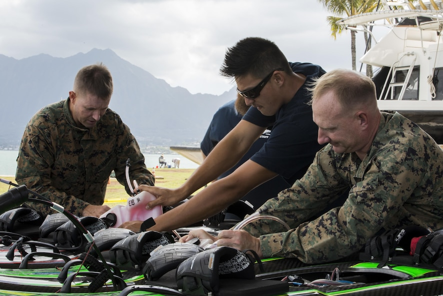 Marines and other personnel make last-minute inspections on self-powered surfboards before a demonstration at Marine Corps Base Hawaii.