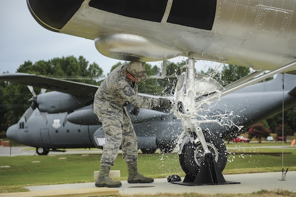 U.S. Air Force Master Sgt. Matthew Tabor, 314th Maintenance Group quality assurance chief inspector, smashes a bottle to christen an H-21B helicopter in Heritage Park July 14, 2016, at Little Rock Air Force Base, Ark. Volunteers from the 314th Maintenance Group refurbished, transported and installed the H-21B static display. (U.S. Air Force photo/Senior Airman Harry Brexel)