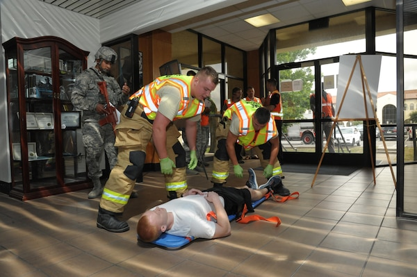 902nd Civil Engineer fire department personnel provide treatment to a simulated victim during an active shooter exercise at Joint Base San Antonio-Randolph July 12. The active shooter exercise tested the threat response time and effectiveness of Joint Base San Antonio's emergency responders and support agencies. The exercise replicated possible real-world events and was designed to enhance training and readiness of JBSA emergency responders during threats to the installation and units.