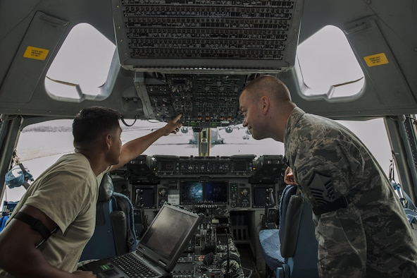 U.S. Air Force Staff Sgt. Arsonio Arthur, 733rd Air Mobility Squadron instrument flight controls systems craftsman, monitors the power of a C-17 Globemaster during a cargo load as Master Sgt. Daniel Hegar, 733rd AMS quality assurance office superintendent, supervises July 6, 2016, at Kadena Air Base, Japan. The 733rd AMS QA office monitors maintenance on the C-17 and the C-5 Galaxy to ensure safe transportation of cargo and troops. (U.S. Air Force photo by Airman 1st Class Lynette M. Rolen)