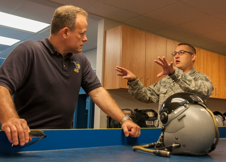 TUCSON, Ariz.—Tech Sgt. Kyle Hoagland, aircrew flight equipment technician at the 162nd Operations Group, right, discusses the changes in helmet technology with the wing's newest honorary commander, Ron Garan. As a former fighter pilot, Garan heard pilots and support personnel describe their experiences here at the 162nd Wing and how it fits in with the total force structure. Garan is the chief pilot at World View, a Tucson-based company that plans to operate commercial near-space flight for passengers as well as scientific research via balloon. (U.S. Air National Guard photo by Capt. Logan Clark)