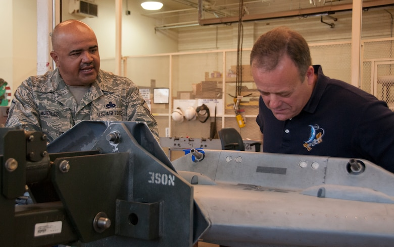 TUCSON, Ariz. – Master Sgt. Antelmo Morales, 162nd Maintenance Group armament flight aircraft systems ordnance mechanic, talks to the newest honorary commander, Ron Garan, about a wing weapons pylon that is being maintained. Garan is the chief pilot at World View, a Tucson-based company that plans to operate commercial near-space flight for passengers as well as scientific research via balloon. Garan retired from active duty Air Force, and toured the base to get a feel for the Air National Guard and talk to Airmen about drill weekend and their units' missions.  (U.S. Air National Guard photo by Staff Sgt. Gregory Ferreira)