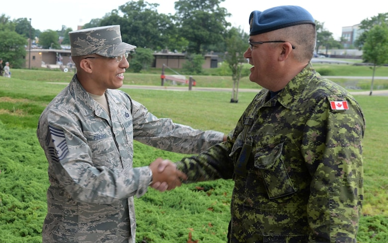 Air Force District of Washington First Sergeant Chief Master Sgt. Manny Pineiro greets Canadian Air Force Chief Warrant Officer Pierrot Jetté as he arrives at the Senior Enlisted Leader International Summit (SELIS) on Joint Base Andrews, Md., July 13, 2016. The SELIS is a forum of international senior enlisted leaders hosted by Chief Master Sergeant of the Air Force James A. Cody. (U.S. Air Force photo/ Tech. Sgt. Matt Davis)