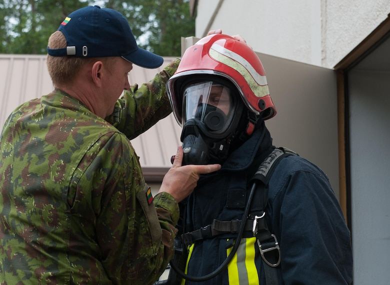 Lithuanian air force Staff Sgt. Valdas Parnarauskas, fire and rescue section commander, helps LAF Capt. Egidijus Rastikis, safety representative, equip firefighter gear before participating in a 435th Construction and Training Squadron-led training exercise July 11, 2016, at Ramstein Air Base, Germany. The 435th CTS provides sufficient training equipment and grounds for its allies to train while receiving guidance and equipment from U.S. Airmen to maintain a constant standard of mission-readiness across Europe.