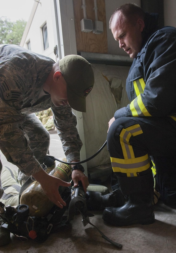 """Lithuanian air force Major Tomas Zukauskas, firefighter, takes his gear off with the help of U.S. Air Force Staff Sgt. Anthony Montano, 435th Construction and Training Squadron contingency firefighting operations instructor, after participating in a training exercise July 11, 2016, at Ramstein Air Base, Germany. The training included close-quarters maneuverability that involves multi-level platforming and retrieving """"training dummies"""" as they simulate saving people out of a trapped situation."""