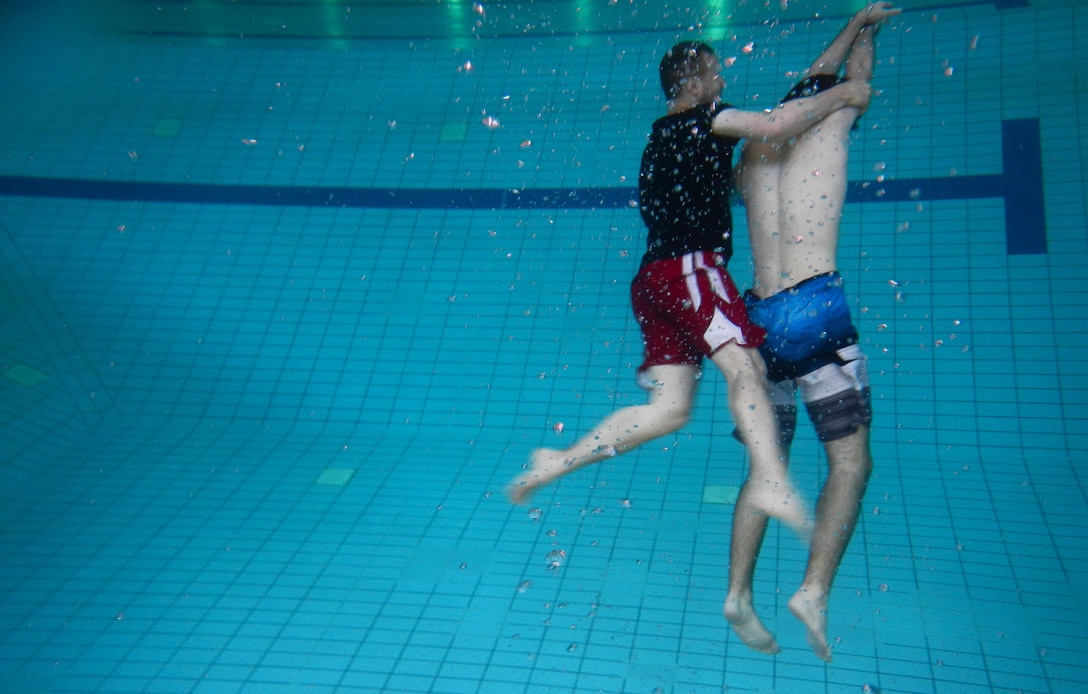 Andrew Broadwater, Ramstein Aquatic Center supervisory recreation specialist lifeguard and lifeguard course instructor, demonstrates a rescue of a victim on the bottom of the pool July 14, 2016, at Ramstein Air Base, Germany. The lifeguard course taught students how to perform rescues for victims that are conscious or unconscious, face up or face down and on the surface or on the bottom of the pool. (U.S. Air Force photo/Airman 1st Class Tryphena Mayhugh)