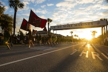 """New Marines run under the iconic """"We Make Marines"""" sign during a traditional motivational run through the streets of Parris Island, S.C."""