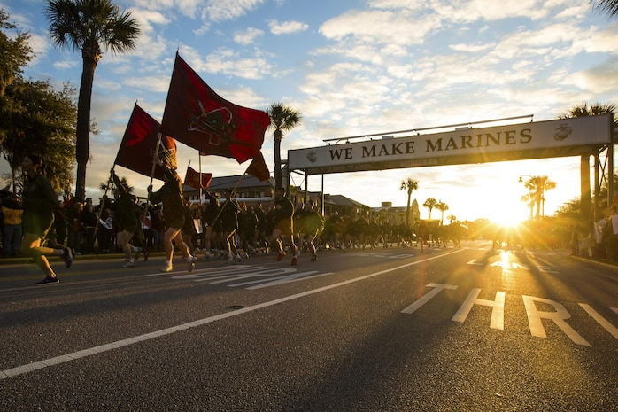 "New Marines run under the iconic ""We Make Marines"" sign during a traditional motivational run through the streets of Parris Island, S.C."