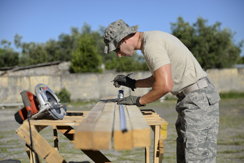 Senior Airman Mark Perna, a heavy equipment operator with the New Jersey Air National Guard, measures lumber used to build braces for pouring concrete steps at a school near Vau i Dejës, Albania, July 8, 2016. Civil engineers with the 177th Fighter Wing traveled to Albania on a deployment for training and worked on humanitarian and civic assistance renovation projects. Facilitated by the U.S. Army's 457th Civil Affairs Battalion, the training gave civil engineers opportunities to learn unique construction techniques and a way to enhance the partnership between Albania and the U.S. (U.S. Air National Guard photo/Master Sgt. Andrew J. Moseley)