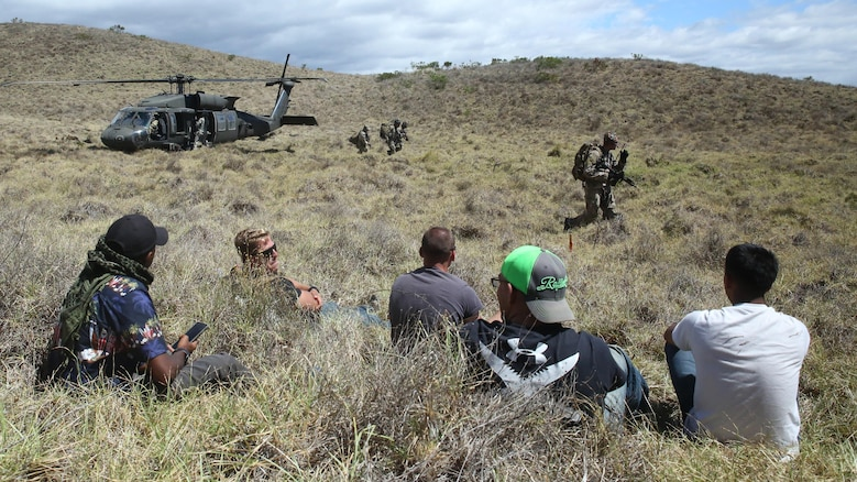 Marines wait for simulated aid during a humanitarian exercise at an improvised landing zone near the Pohakuloa Training Area, Hawaii, July 9, 2016, during Rim of the Pacific 2016. Twenty-six nations, 49 ships, six submarines, about 200 aircraft, and 25,000 personnel are participating in RIMPAC 2016 from June 29 to Aug. 4 in and around the Hawaiian Islands and Southern California. The world's largest international maritime exercise, RIMPAC provides a unique training opportunity while fostering and sustaining cooperative relationships between participants critical to ensuring the safety of sea lanes and security on the world's oceans. RIMPAC 16 is the 25th exercise in the series that began in 1971.
