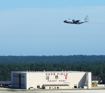 The 440th Airlift Wing's last remaining aircraft tilts its wing as it makes a final pass over the Pope Field hangar on its departure from Pope, June 29, 2016. The unit had been in the process of inactivation for several months and its other C-130s had been redistributed to other units. (Courtesy photo)