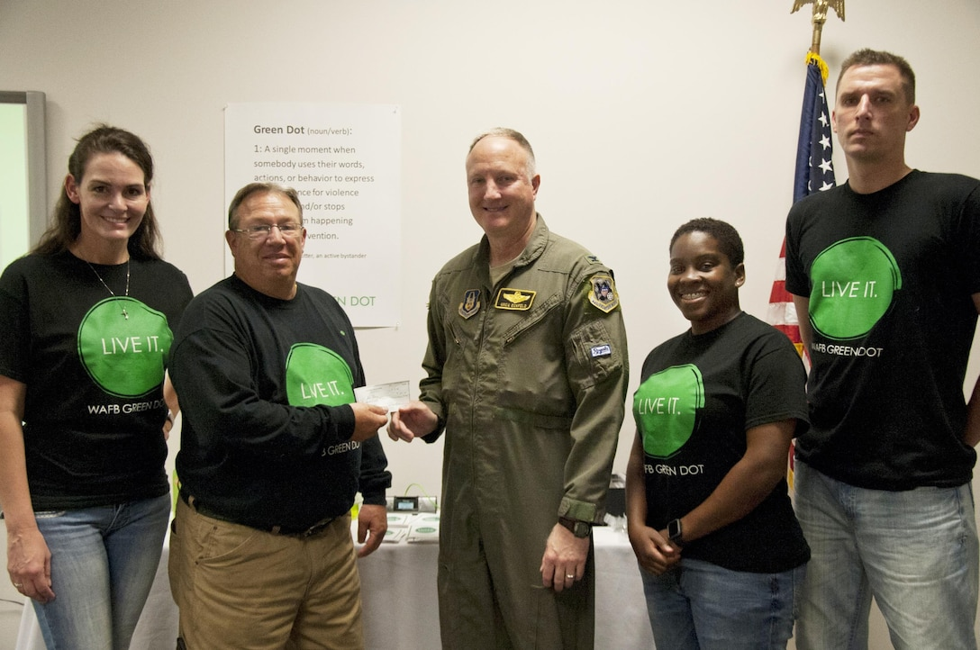 U.S. Air Force Col. Gregory Eckfeld, 442nd Fighter Wing vice commander, center, presents a check to Robin Smith, director of the 509th Bomb Wing Airman and Family Readiness Center, to support the Green Dot program at Whiteman Air Force Base, Mo., July 14, 2016. Eckfeld is representing the 442nd FW Human Resources Development Council that is donating money in support of Green Dot.  (U.S. Air Force photo by Senior Airman Missy Sterling)