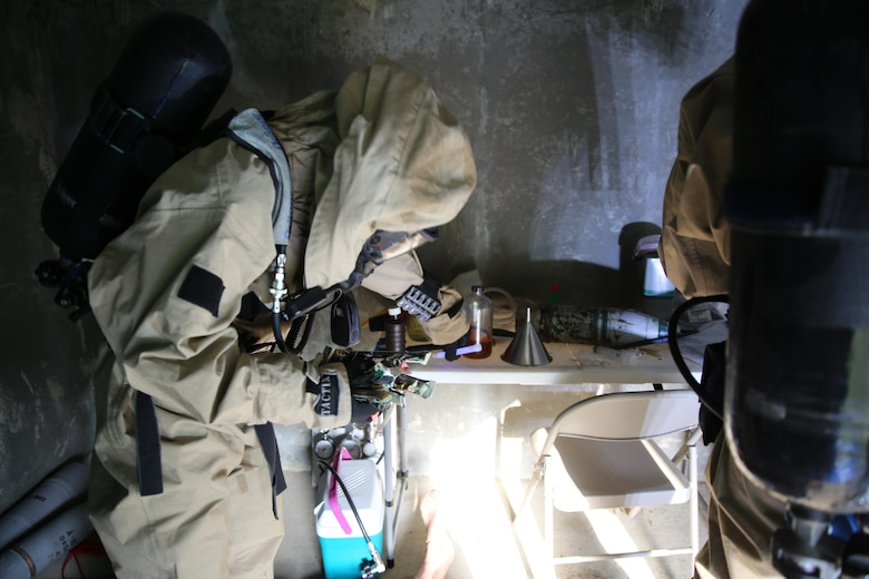 Lance Cpl. Ryan Shriver places chemical lights around a simulated incident site during a training exercise at Marine Corps Air Station Cherry Point, N.C., July 12, 2016. The training further refined the interoperability between MCAS Cherry Point's Explosive Ordnance Disposal and 2nd Marine Aircraft Wing's Chemical, Biological, Radiological and Nuclear Defense. Shriver is a CBRN defense specialist with Marine Wing Headquarters Squadron 2. (U.S. Marine Corps photo by Lance Cpl. Mackenzie Gibson/Released)