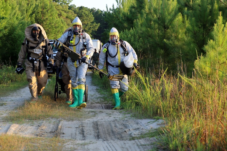 Marines with Marine Corps Air Station Cherry Point's Explosive Ordnance Disposal and 2nd Marine Aircraft Wing's Chemical, Biological, Radiological and Nuclear Defense walk toward a simulated incident site during a training exercise at MCAS Cherry Point, N.C., July 12, 2016. The training further refined the interoperability between EOD and CBRN. (U.S. Marine Corps photo by Lance Cpl. Mackenzie Gibson/Released)