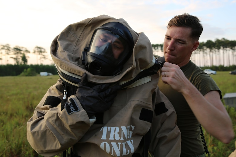 Sgt. Jarrod Roper receives help from Sgt. Christian Nelson as he dons his gear during a training exercise at Marine Corps Air Station Cherry Point, N.C., July 12, 2016. The training further refined the interoperability between MCAS Cherry Point's Explosive Ordnance Disposal and 2nd Marine Aircraft Wing's Chemical, Biological, Radiological and Nuclear Defense. Roper and Nelson are CBRN defense specialist with Marine Wing Headquarters Squadron 2. (U.S. Marine Corps photo by Lance Cpl. Mackenzie Gibson/Released)