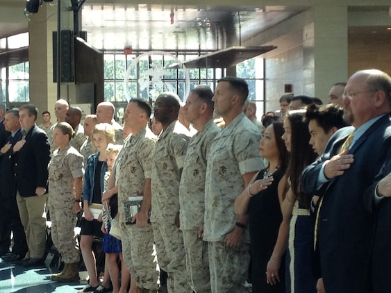 Attendees and participants stand at attention during the playing of the National Anthem at the change of command ceremony for MCIOC at the National Museum of the Marine Corps on June 30, 2016.