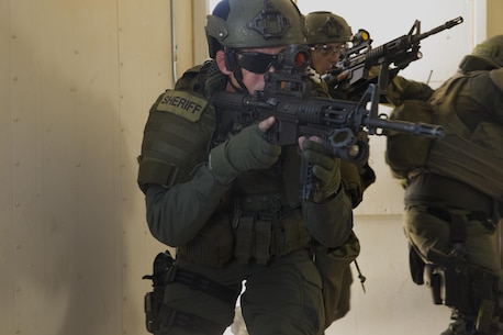 A deputy sheriff with the San Bernardino County Sheriff's Department Special Weapons and Tactics Team clears a building in the military operations in urban terrain facility at Range 800 aboard Marine Corps Air Ground Combat Center, Twentynine Palms, Calif., July 12, 2016. The Combat Center's Special Reaction Team hosted the cross-training to provide SBCSD with insight of the Marine Corps' tactics capabilities. (Official Marine Corps photo by Cpl. Medina Ayala-Lo/Released)