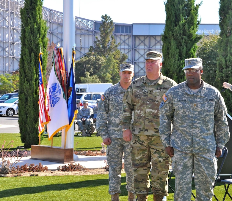 Lt. Col. Michael Stewart (left), company commander, Headquarters and Headquarters Company, 63rd Regional Support Command, Maj. Gen. Nick Tooliatos (center), commanding general, 63rd RSC and outgoing HHC commander Maj. Derrick Carter (right) pause momentarily following the ceremonial passing of the colors, during a change of command ceremony, July 13, Armed Forces Reserve Center, Mountain View, Calif.