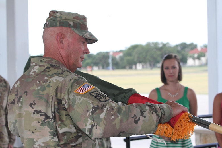 JBSA FORT SAM HOUSTON- Command Sergeant Major Paul Swanson unveils Major General Jones' Officer Flag during the promotion ceremony at the MacArthur Parade Field. The flag will always accompany the General Officer everywhere he goes, a tradition authorized by the War Department in August 1903.
