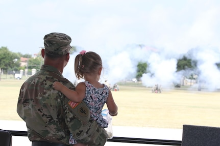 """JBSA FORT SAM HOUSTON- Major General Jones and granddaughter look as the cannons fire at the conclusion of the ceremony at the MacArthur Parade Field. The firing of the cannons symbolizes the generals """"Texas farewell"""", said Command Sergeant Major Paul Swanson. (Photo by Spc. Eddie Serra of the 205th Press Camp Headquarters)"""