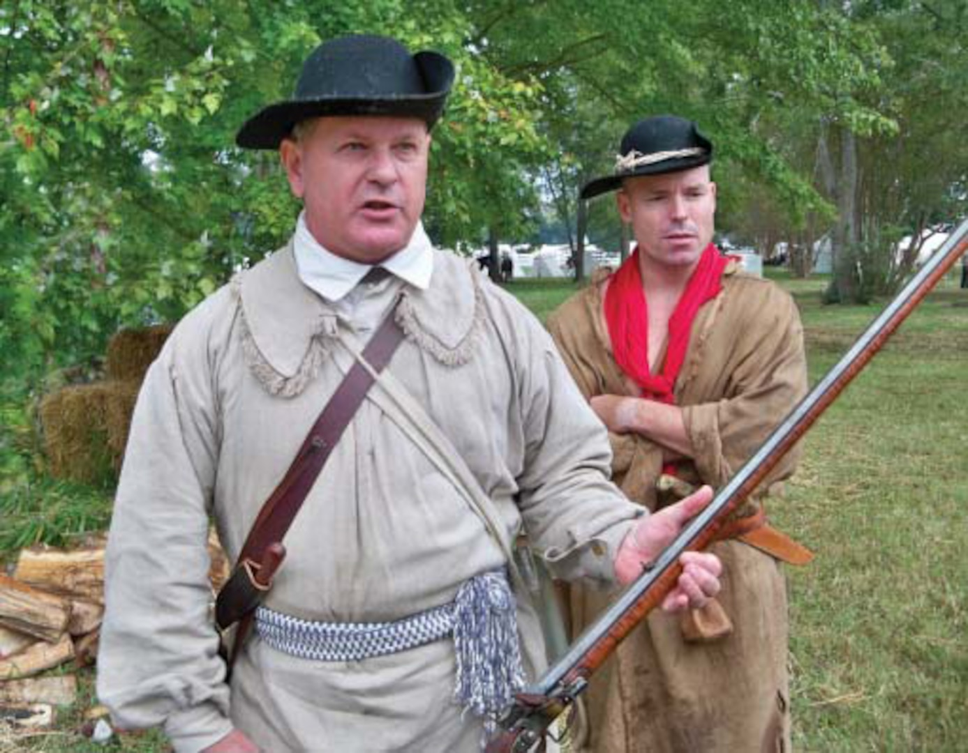 """Dressed in typical attire of back-country riflemen, Revolutionary War living historians in Virginia prepare for a reenactment. The round hats and hunting shirts are the same as those described in the accounts of the first riflemen within companies such as the Berkeley County Rifles who made the """"Beeline to Boston."""""""